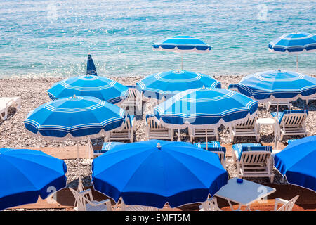Blue umbrellas and chairs on pebble beach in Nice, France. - Stock Photo