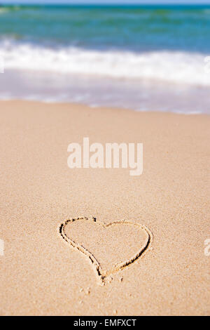 Image of a painted heart in the sand on the beach of the Baltic Sea in Germany - Stock Photo