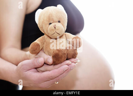 mom and dad prepare bear doll for a new life - Stock Photo