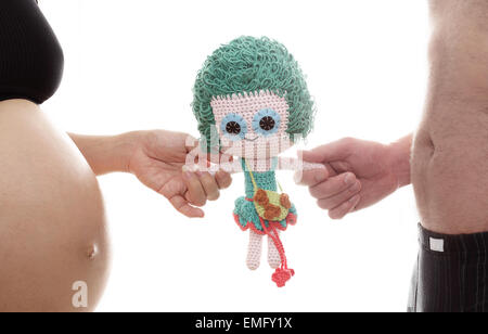 mom and dad prepare girl doll for a new life - Stock Photo