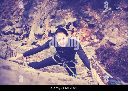 Vintage style filtered picture of a young woman climbing wall. - Stock Photo