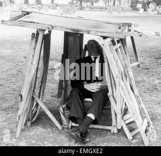 Man using whatever improvised materials he can find including folded up deckchairs to build a shelter from the relentless - Stock Photo