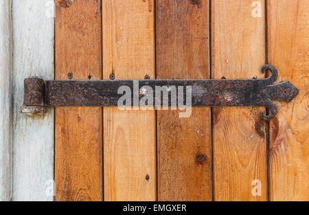 Old wooden door with an old cast iron door hinges - Stock Photo