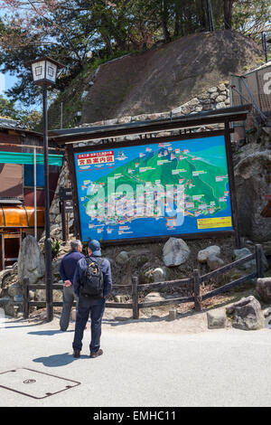 HATSUKAICHI, MIYAJIMA, JAPAN - CIRCA APR, 2013: An information board with a map and routes for visitors is on street - Stock Photo