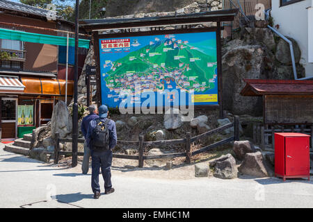 HATSUKAICHI, MIYAJIMA, JAPAN - CIRCA APR, 2013: An information board with a map and routes for tourists is on street - Stock Photo