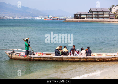 Small boat for sea cruise through the red sacred torii gate, passengers are boarding from the beach. The Miyajima - Stock Photo