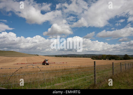 A farmer spraying crops in a Wheat field with barbed wire fencing under a cloudy sky - Stock Photo