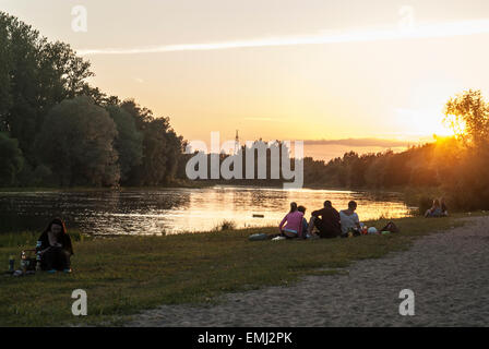 Students having a party on a summer evening with sunset on the banks of Emajogi river on the outskirts of Tartu - Stock Photo