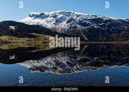 Reflection of the mountains meeting the sea at Granvinsvatnet, in Hardanger, Norway. - Stock Photo