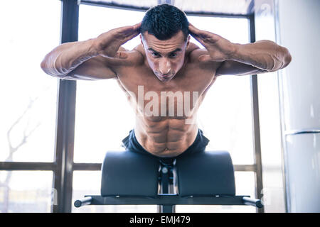 Handsome muscular man flexing back muscles on bench in gym - Stock Photo
