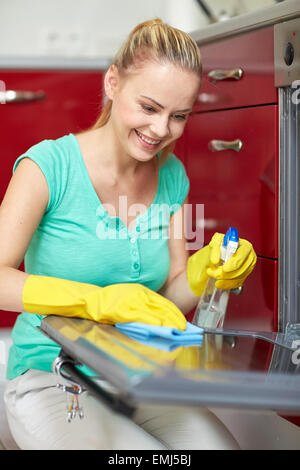 happy woman cleaning cooker at home kitchen - Stock Photo