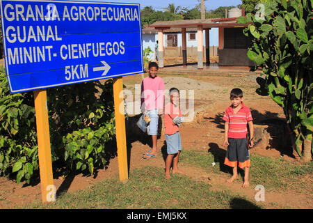 Cuban children boys by a road direction sign in Playa Giron Cuba - Stock Photo
