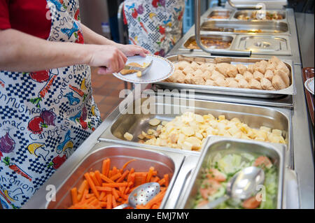 Dinner ladies at a UK primary school serve up hot dinners at lunchtime - Stock Photo