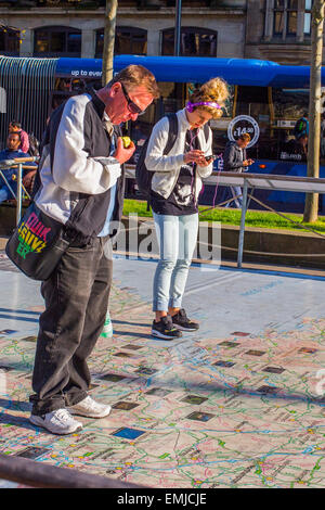 Leeds, UK. 21st April, 2015. UK Weather: People walking on a sunlit map of the UK in Leeds city centre. The map - Stock Photo