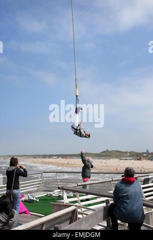 Woman hanging from a bungee jump cord at Scheveningen beach pier tower in Hague, (Den Haag), Holland, Netherlands. - Stock Photo