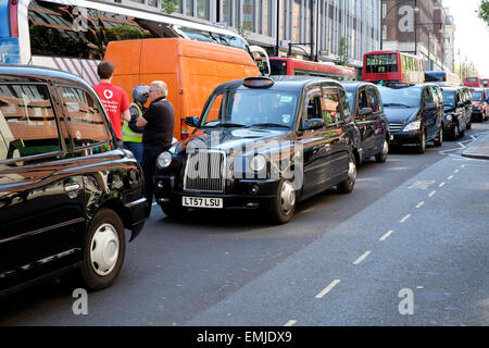 Oxford Street blocked by  taxi drivers as they protest against illegal mini cabs. - Stock Photo