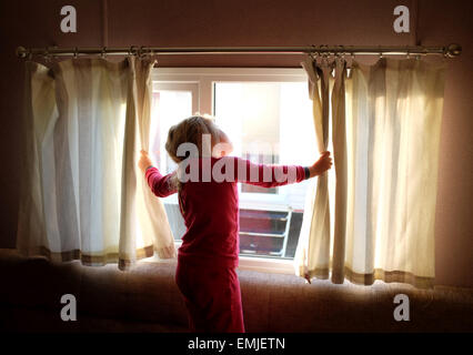 A sleepy young girl in pyjamas opens the curtains to look out of the window at the start of a new day - Stock Photo
