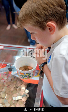 A boy playing putting Two pence coins in a tipping point machine in a seaside arcade - Stock Photo