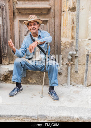 A Cuban male senior citizen gestures with his right hand as he leans on his cane and sits on a concrete step by - Stock Photo