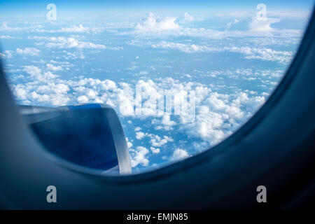 View from a window seat, passenger airplane, clouds and sky - Stock Photo