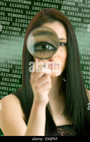 Woman looking through a loupe at a computer virus concept - Stock Photo