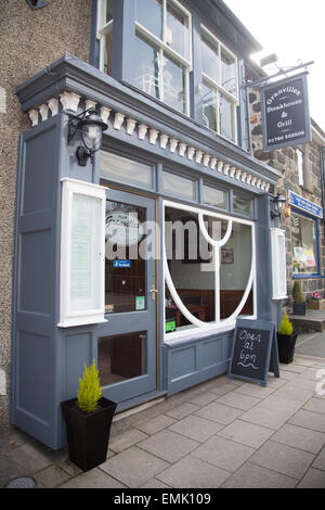 Freshly painted bistro restaurant on Criccieth High Street with original Victorian shop front and ornate window - Stock Photo