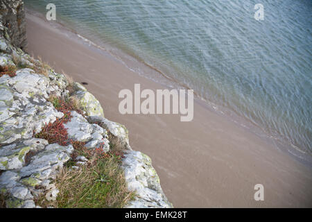 View from cliff edge at Pen-y-Banc, Bort-y-Gest, Porthmadog showing rock edge, and drop down to sandy beach and - Stock Photo
