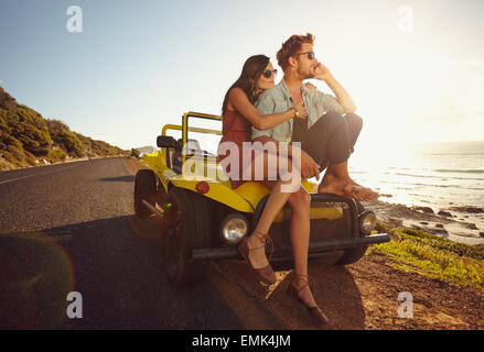 Relaxed young couple sitting on the hood of their car alongside a open coastal road with man answering a phone call - Stock Photo