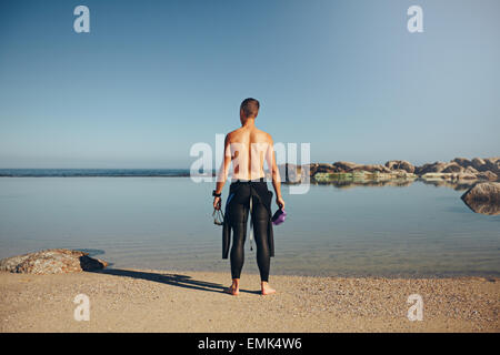 Rear view of young athlete on beach preparing to swim. Young triathlete preparing for a race wearing a wetsuit prior - Stock Photo