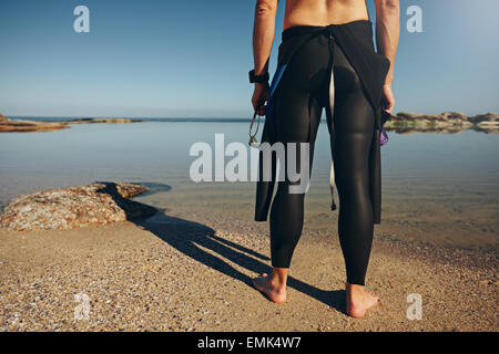 Rear view of man standing on lake wearing wetsuit. Cropped shot of a triathlete getting ready for a race. - Stock Photo