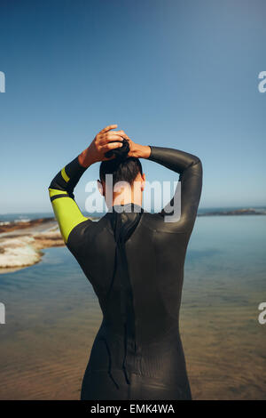 Rear view of young triathlete on the lake preparing for a race wearing a wetsuit. Female triathlon athlete tying - Stock Photo