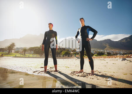 Portrait of a determined male and female triathletes looking into the distance. Young man and woman standing at - Stock Photo