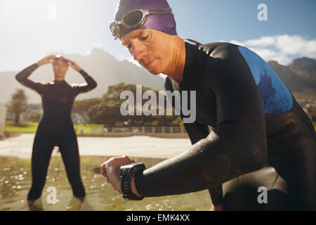Focused young man checking his watch while in wetsuit at the lake. Man looking at watch after practice run. Triathletes. - Stock Photo