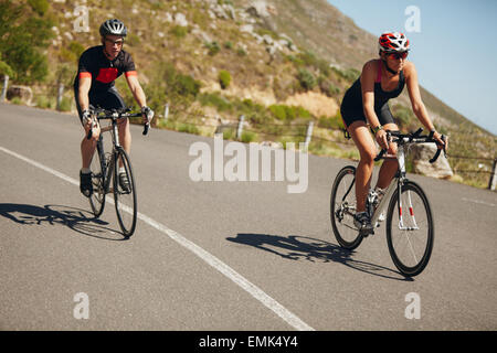 Woman competing in the cycling leg of a triathlon with male competitor. Triathletes riding bicycle on open road. - Stock Photo