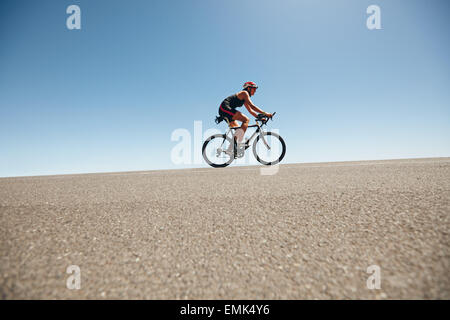 Female cyclist on a country road training for triathlon. Young woman riding bicycle up hill. - Stock Photo