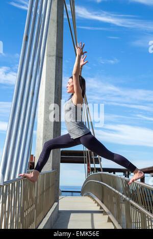 Virabhadra yoga pose balanced on a bridge, La Jolla, California - Stock Photo