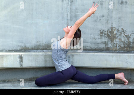One Legged King Pigeon Yoga pose variation performed outdoors on a bench, San Diego, California - Stock Photo