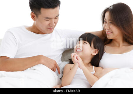 A family of three sat on the bed in the bedroom - Stock Photo
