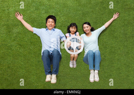 The joy of a family of three in lying on the grassland is holding the steering wheel model - Stock Photo