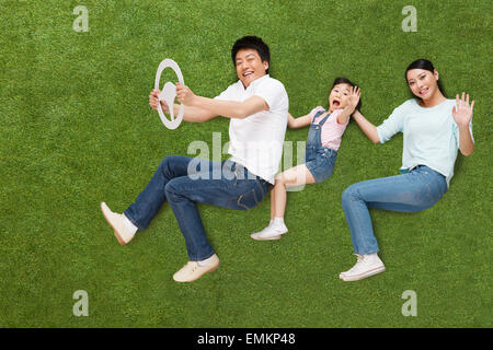 The joy of a family of three in the grass driving - Stock Photo