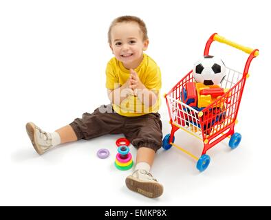 Happy little boy sitting on ground, and playing. New toys in small shopping cart - Stock Photo