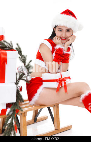 Dressed in a Santa suit young woman sitting on a sled - Stock Photo