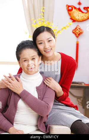 Daughter hug mother's shoulder and sat on the sofa - Stock Photo
