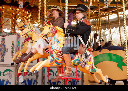 Middle aged caucasian couple having fun on a roundabout or carousel, Norfolk, UK - Stock Photo