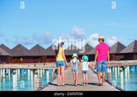 Back view of beautiful family on wooden jetty during summer vacation at luxury resort - Stock Photo