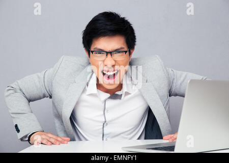 Angry young man sitting at the table with laptop and screaming on camera over gray background - Stock Photo
