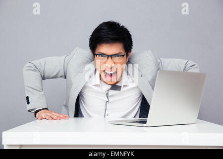 Angry young man sitting at the table with laptop and looking at camera over gray background - Stock Photo
