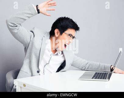 Angry young businessman in glasses sitting at the table with laptop over gray background - Stock Photo