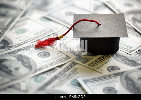 Graduation mortar board cap on one hundred dollar bills concept for the cost of a college and university education - Stock Photo