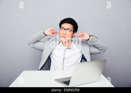 Handsome asian businessman sitting at the table and covering his ears over gray background - Stock Photo